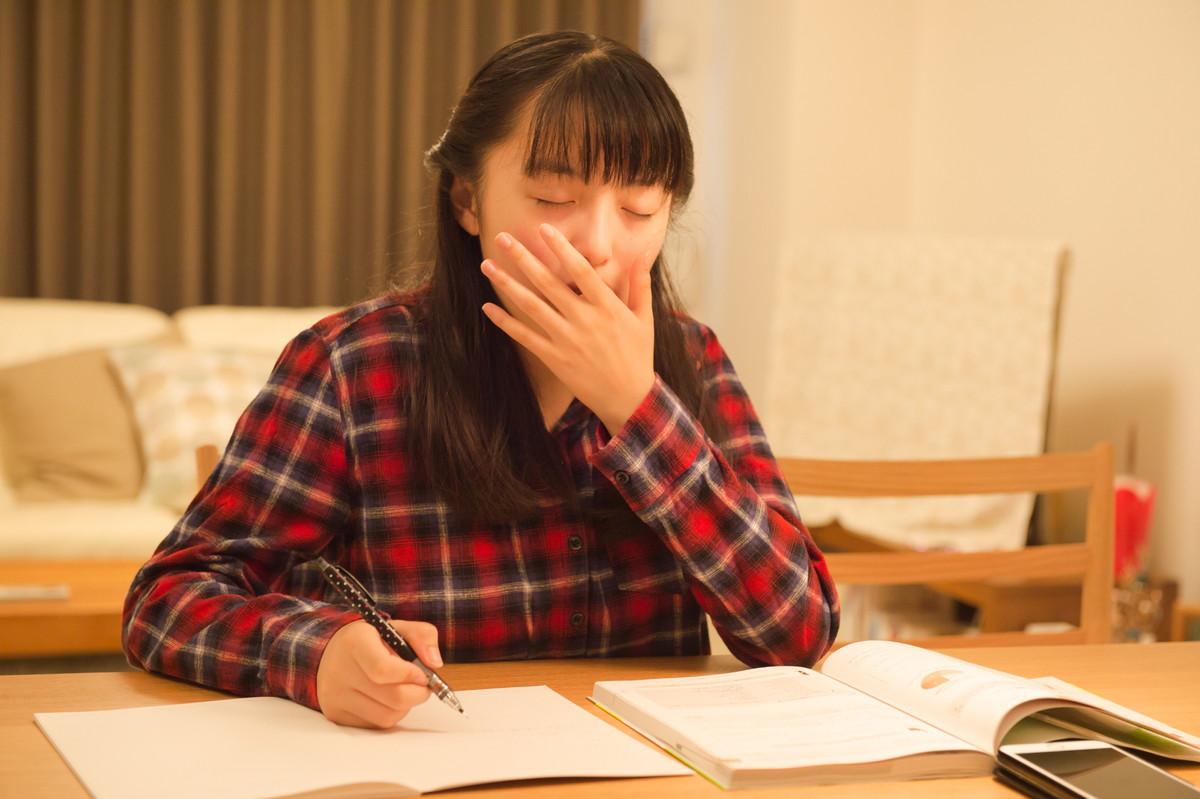 部屋で勉強する中学生